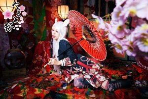 和傘を持ちながらくつろぐ白狐コスプレの女性